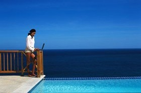Woman with Laptop by the Pool and Ocean